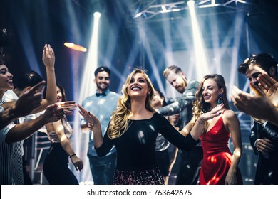 Shot of a happy young woman on the dancefloor with friends
