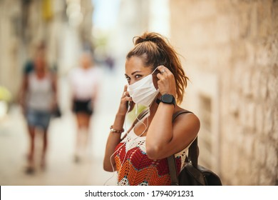 Shot of a happy young woman with protective mask spending time on vacation and exploring a Mediterranean city at corona pandemic.