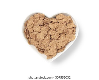 shot of a heart shaped cereal bowl full of bran flakes cut out on a white background with a clipping path and copy space.