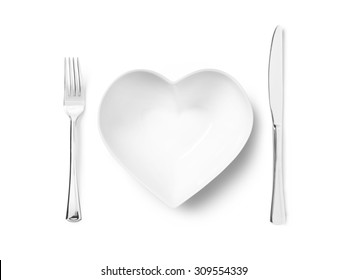 Shot of a heart shaped plate or bowl with a silver knife and fork implying a love of healthy eating. The image has copy space and a clipping path for each of the items.
