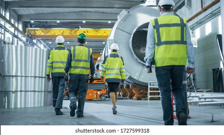 Shot of Heavy Industry Engineers and Workers Walking through Pipe Manufacturing Factory. Modern Facility for Design and Construction of Oil, Gas and Fuels Transport Pipeline. Low Angle