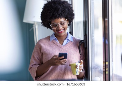 Shot of hipster young businesswoman using her mobile phone while standing next to the window in the office.