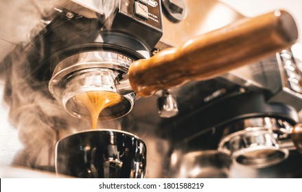 A shot of hot espresso coffee is pulled through group head and portafilter with a wooden handle into a black coffee cup surrounded by steam