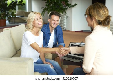 Shot of an investment advisor businesswoman consulting with her clients. Middle aged woman and professional agent shaking hands after making deal.