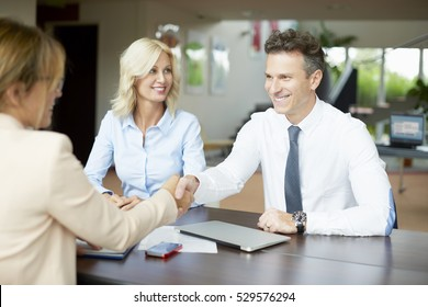 Shot of an investment advisor shaking hands with smiling man while consulting with middle aged couple about financial savings.