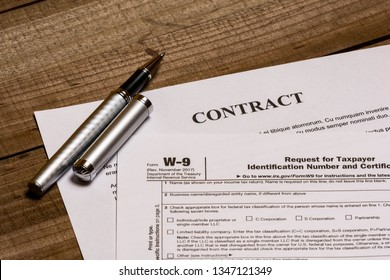 Shot of a IRS tax form W-9 and a generic contract.