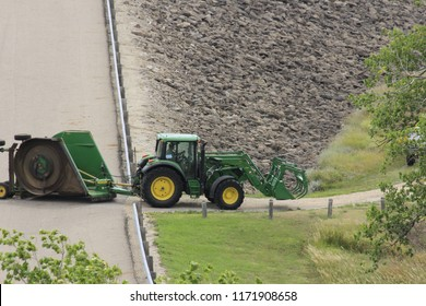 A shot of a John Deere Tractor with a mower,front end loader with a bale grapple attachment on it that's on a road at Wilson Lake, south of Lucas Kansas USA on 8-5-2018.