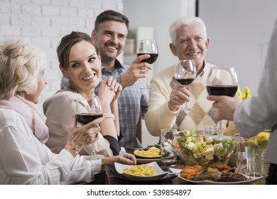 Shot of a joyful family drinking red wine and celebrating dinner