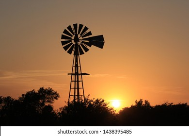 A shot of a Kansas colorful Sunset with a Windmill silhouette with a golden and orange sky out in the country with tree silhouette's.