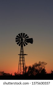 A shot of a Kansas Sunset in the evening with a Windmill Silhouette with trees north of Hutchinson Kansas USA.