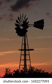 A shot of a Kansas Sunset thats bright and colorful with clouds,trees, and a Windmill silhouette thats north of Hutchinson Kansas USA out in the country.