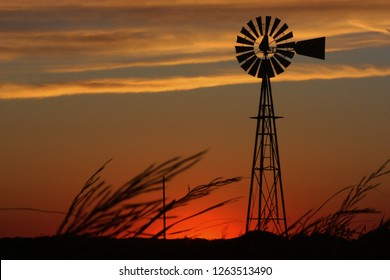 A shot of a Kansas Windmill Sunset Silhouette that's bright red with white clouds that's west of Nickerson Kansas USA out in the country.