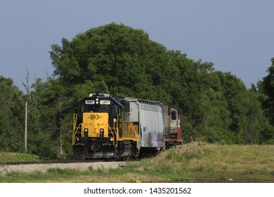 A shot of a K&O  Train Engine that's going down the track to move more train cars that's yellow, and black with a red engine on the back side . That's west of Hutchinson Kansas USA on 6-26-2019.