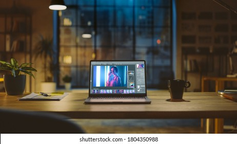 Shot of a Laptop Computer in the Modern Office Showing Photo Editing Software. In the Background Warm Evening Lighting and Open Space Studio with City Window View