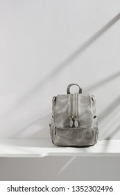 Shot of light gray denim rucksack with wax coating and flap top, adorned with zippers, isolated in middle on white platform over gray wall with stripy shadow on background. Trendy women's accessory.