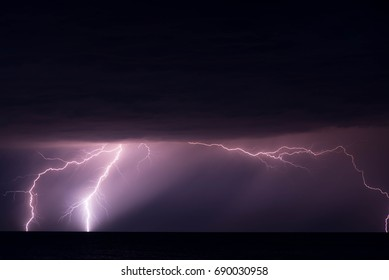 Shot of a lightning strike in the sea during a thunderstorm with heavy rain. Shot is taken at the seaside of the Baltic Sea.