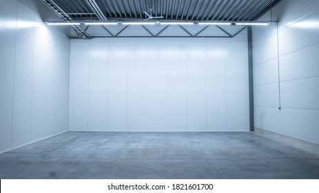 Shot of a Lit Empty Warehouse with Gray Concrete Floor, White Metall Wals, and Steel Ceilings. Great Room for Small Factory or Production Line.