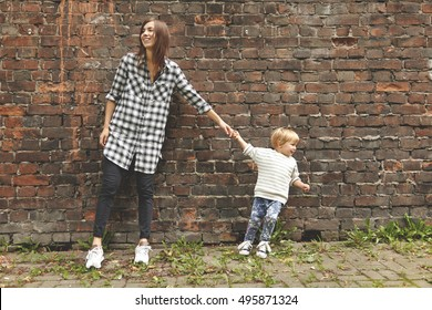 Shot of little blond boy and young girl on a walk near brick wall. Tiny kind pulling grown-up aunt to go away. Caucasian girl in checked shirt stay stubborn. Two persons looking at opposite sides.