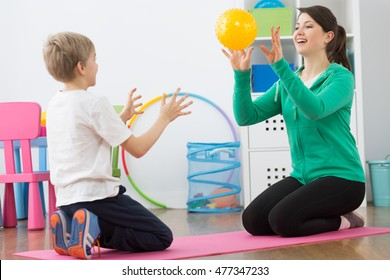 Shot of a little boy and his physiotherapist playing with a ball