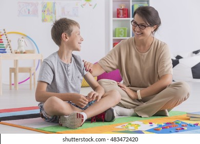 Shot of a little boy and a young woman sitting on a floor and smiling at each other