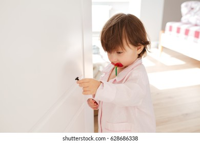 Shot of little curious girl with nipple and holding screw in bedroom