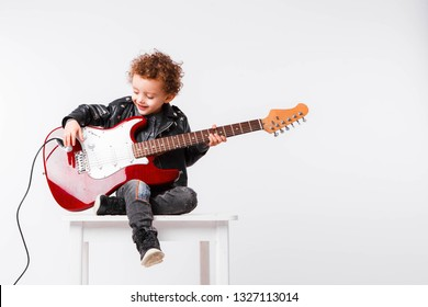 Shot of a little curls boy playing rock music with electric guitar.