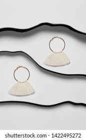 Shot of long dangle earrings, adorned with beaded milky tassels in the view of a waver. The accessory set is isolated asymmetrically against snow-white background between black faux leather stripes.