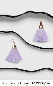 Shot of long earrings with pendants in view of metal triangle with lavender-blue tassels. The accessory set is isolated asymmetrically against white background between black faux leather stripes.