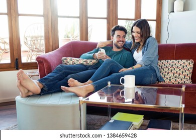 Shot of lovely young couple using they mobile phone while sitting on sofa at home.