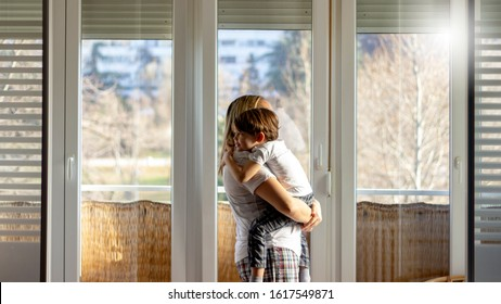 Shot of loving mother carrying her boy at home.Rear view portrait of family on balcony looking through the window.Shot of single mother and her adorable little son looking out the window at home.