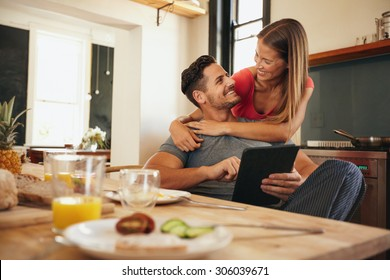 Shot of loving young couple in kitchen by breakfast table in morning. Man using digital table while woman hugging him from behind, both looking at each other smiling.