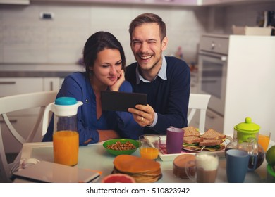 Shot of loving young couple in kitchen by breakfast table in morning using digital tablet