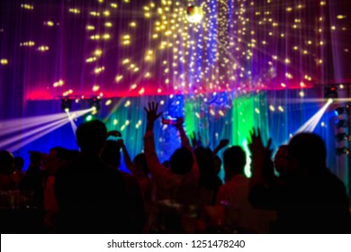 Shot in low light blurred concept night scene in concert party with audience and colourful led lighting