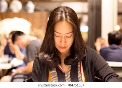Shot in low light woman customer looking menu waitress taking order in restaurant