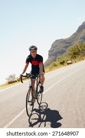 Shot of a male cyclist riding down a country road. Triathlete cycling on a bicycle.