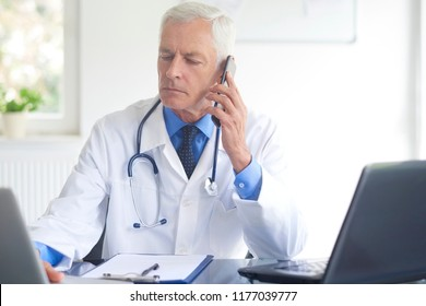 Shot of male doctor sitting at constulting room and talking with his patient on phone.
