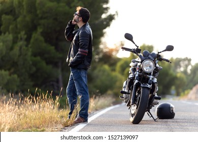 Shot of man biker talking on the phone to the insurance of his motorcycle after having suffered a breakdown on the road.
