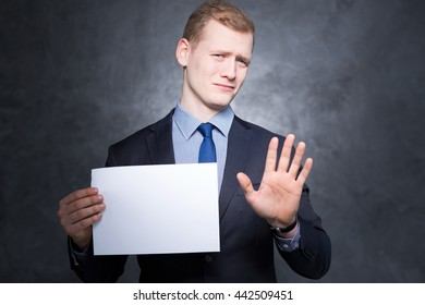 """Shot of a man in a black suit holding an empty sheet of paper and making a """"stop"""" gesture"""