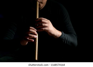 Shot of a man blowing thai style flute, Thai culture, musicology background, music skills learning and education.