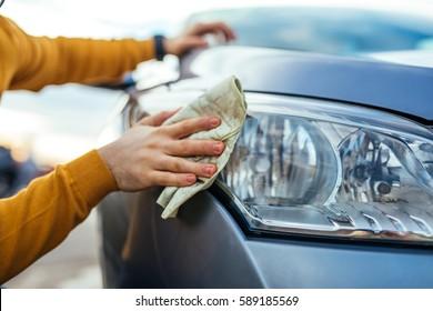 Shot of man polishing his car with a cloth.