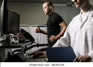Shot of a man running on a treadmill with electrode attachted to his body and a young doctor