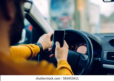 Shot of a man using mobile phone while driving.