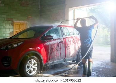 Shot of a man washing his red car under high pressure water. Car cleaning. High pressure water washing. Close up concept.