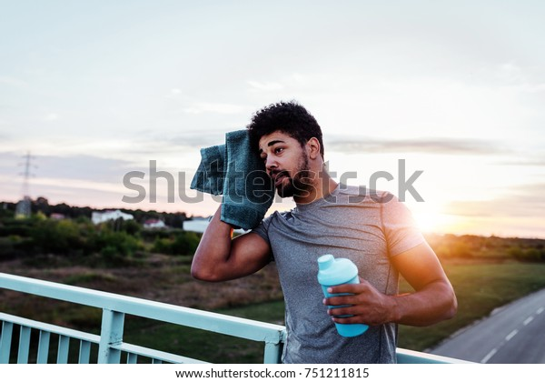 Shot of a man wiping his head , holding bottle of water