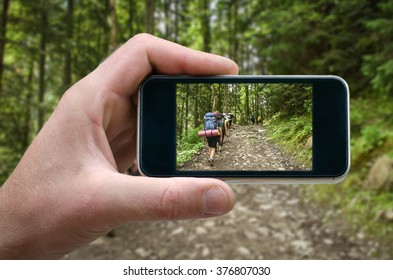 shot of a man's hand holding a smartphone, mountain scenery, nature in the mountain heights Photo by man photographed on a smartphone, the spring in the mountains