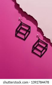 A shot of massive black dangle earrings with volume effect. The stylish set is isolated asymmetrically against the pink background, near pale pink ragged platform. Fashionable women's fashion item.