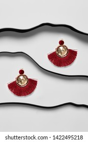 Shot of massive dangle earrings with pendant in view of disk, adorned with deep red needles. The accessory set is isolated asymmetrically on the snowy background between black faux leather stripes.