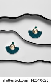 Shot of massive dangle earrings with pendant in view of disk, adorned with emerald needles. The accessory set is isolated asymmetrically on the snowy background between black faux leather stripes.