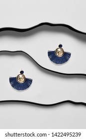Shot of massive dangle earrings with pendant in view of disk, adorned with navy blue needles. The accessory set is isolated asymmetrically on the snowy background between black faux leather stripes.