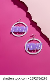 A shot of massive dangle earrings with stylish Boom Pow lettering. The set is isolated asymmetrically against the pink background, near pale pink ragged platform. Fashionable women's fashion item.